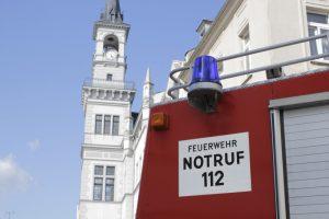 Feruerwehrfahrzeug vor Rathaus im Hintergrund